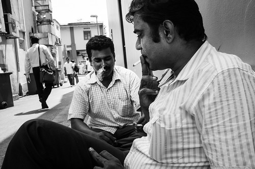 Two men smoking and relaxing in an alley in Little India, Singapore