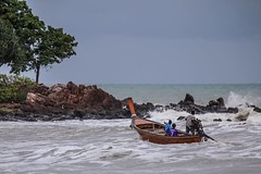 In treacherous waters a longtail boat makes shore on Koh Lanta, Thailand #travel #amazingthailand #ocean