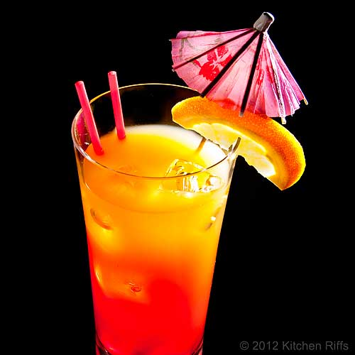 Tequila Sunrise Cocktail in Tall Glass with Orange Slice and Umbrella