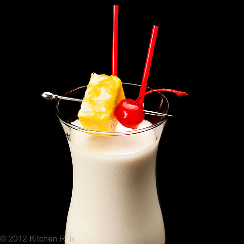 Piña Colada Cocktail with Pineapple and Maraschino Cherry Garnish, Black Background