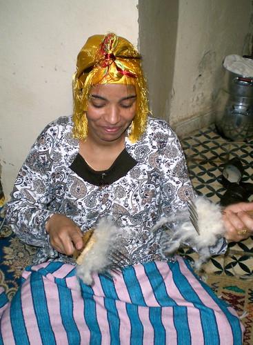 Naima prepares wool to be spun.
