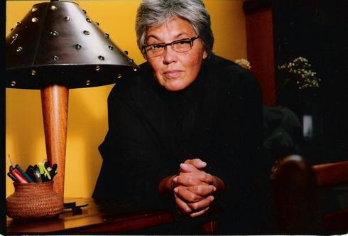 A recent picture of Lourdes Portillo sitting by a lamp. She has short grey hair and glasses and looks at the camera with interest.