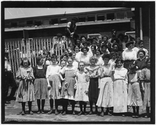 Group of girl workers at the gate of the American Tobacco Co. Young girls obviously under 14 years of age, who work about 10 hours every day except Saturday, May 1910
