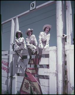 Mrs. Merle K. Stier, Stampede Queen (centre), and two attendants... / La Reine du Stampede Mme. Merle K. Stier (centre) et deux de ses demoiselles...