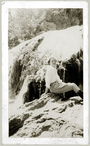 Girl on a rock beside a waterfall