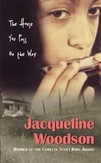 Cover of The House You Pass on the Way by Jacqueline Woodson. Shows a closeup photo of a girl playing harmonica.