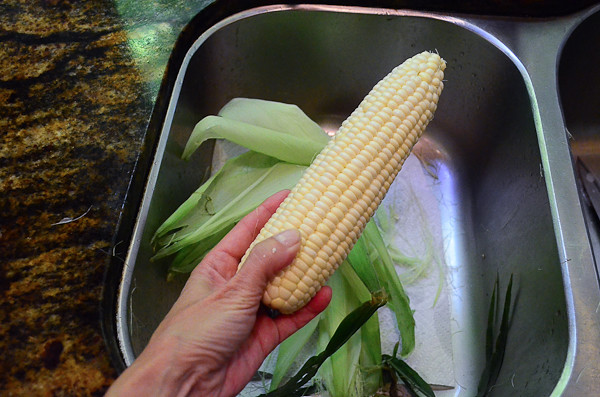 A corn with its husk being removed into the sink.