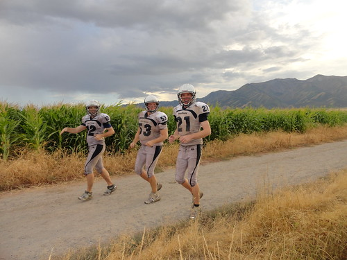 Muddy football players running along corn fields