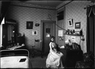 Pomona College student Edith Parker 1903 sits at a desk in her room in Sumner Hall (1903)
