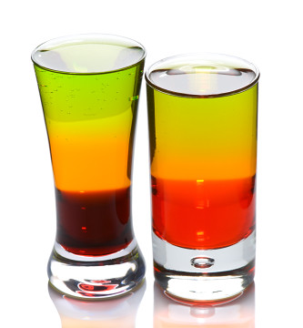 Two shot glasses with layered cocktails