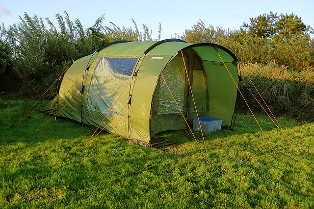 A green tent set up on a campsite
