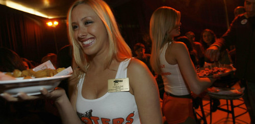 a hooters employee carrying a tray of food and wearing a skimpy uniform