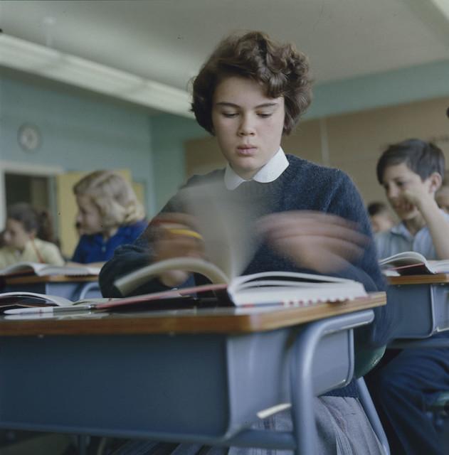 Girl sitting at desk flipping through textbook pages at Putnam School / Fille assise à un bureau feuilletant les pages d'un manuel à l'école Putnam