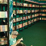 Boy reading in the children's bookshop | Engrossed in a book in the RBS Children's Bookshop