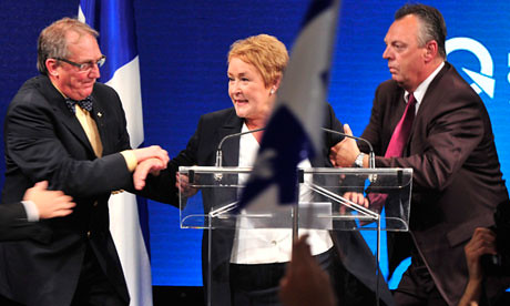 Pauline Marois is whisked off stage after a shooting and arson attack at the rear of the building. She won the elections and will establish a minority government of French separatists in Quebec. by Pan-African News Wire File Photos