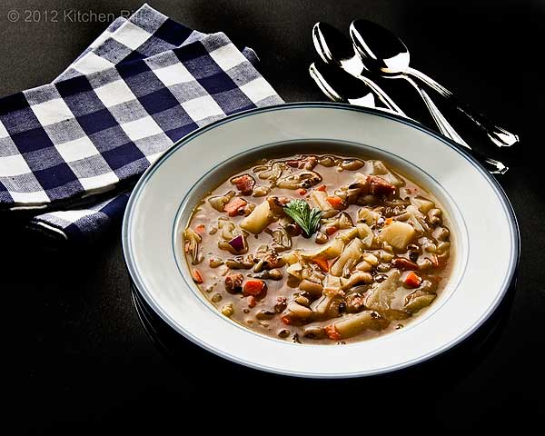 Black-Eyed Pea and Cabbage Soup in Bowl, with napking and spoons