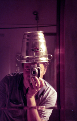 reflected self-portrait with Pentax Espio 160 camera and metal hat by pho-Tony