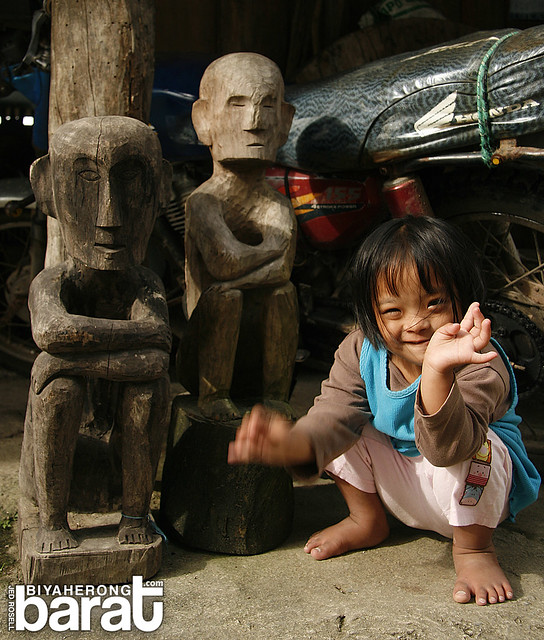 Kid playing with the wooden statues displayed at the Hanging House.