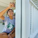 12-032 -- As a Titan to Titan' volunteer during Mission Day, Megan Win '16 painted trim on the front porch at the home of Marilea White '63 in Normal.