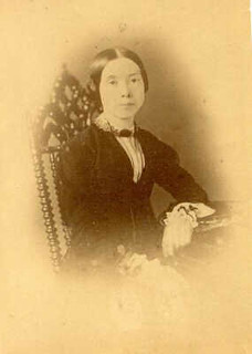 Emily Dickinson sits stiffly in this sepia portrait