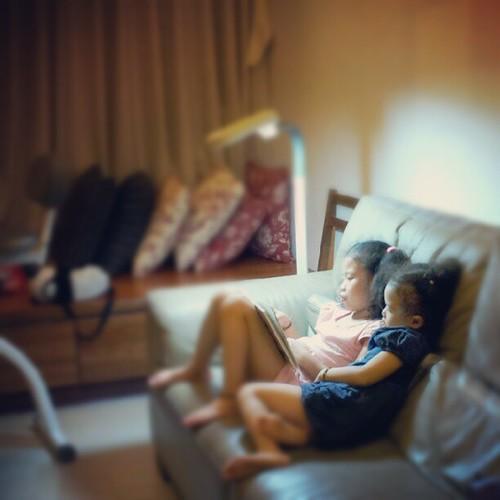20120918 姊姊念故事書給妹妹聽。