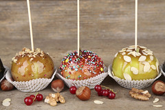 Sweet caramel apples on sticks with berries, on wo…