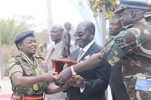 President Mugabe hands over the Mbuya Nehanda trophy to Sergeant Evelyn Fimba who was the overall winner in the women's category of the President's Medal Shoot competition while Air Force of Zimbabwe commander Air Marshal Perrance Shiri looks on. by Pan-African News Wire File Photos