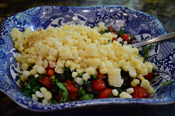 The grilled corn is added to the bowl.
