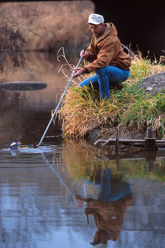 ARS Technician Jeff Nichols collects a water sample from the Walnut Creek watershed in Ames, Iowa.