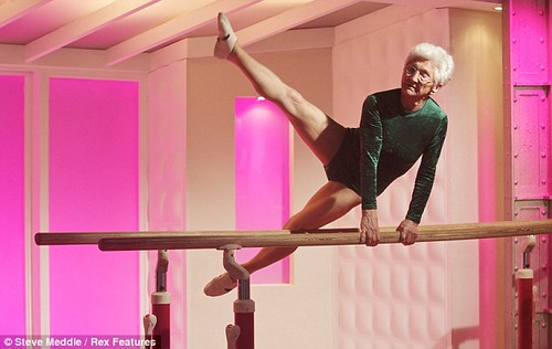 older white woman in a green leotard on the parallel bars