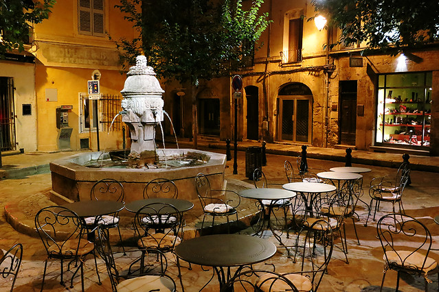 Fountain and restaurant seating in the evening light in Aix-en-Provence, France