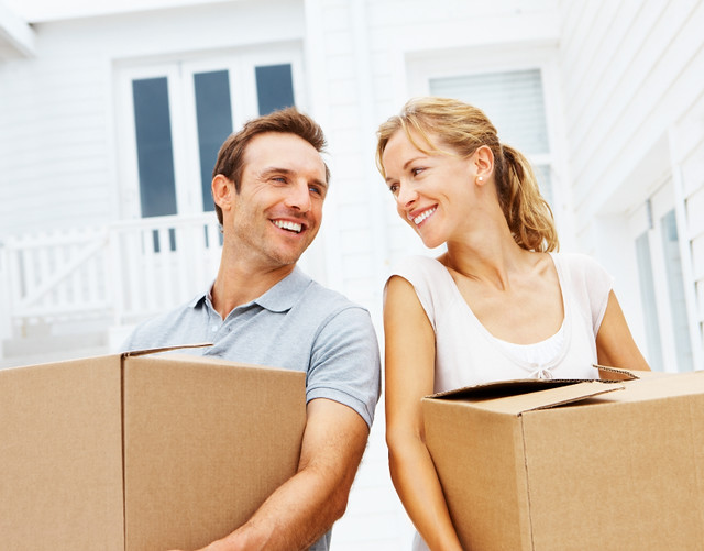 Happy couple with boxes moving in new house
