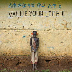 Suri Boy Leaning against a wall covered with Amharic and English Writing, Tulgit, Ethiopia