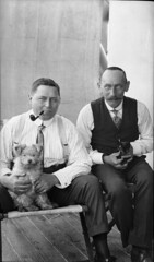 Two crew members holding pet dog and cat