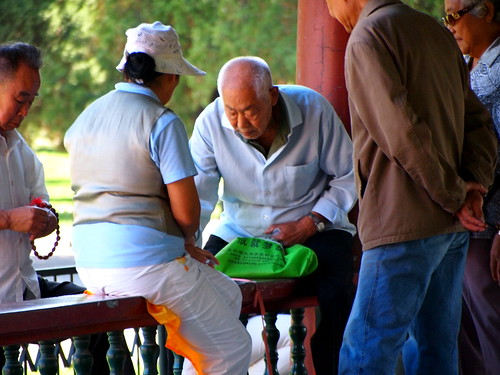 An older gentleman plays cards at the Temple of Heaven.
