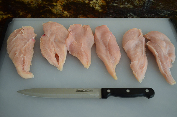 6 chicken breast halves laid out on a cutting board.