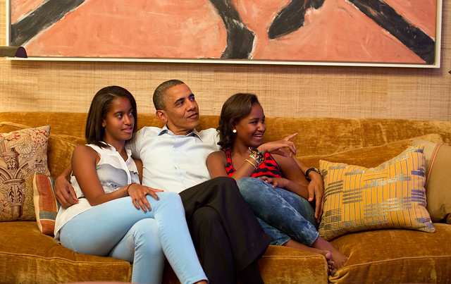image of President Obama and his daughters sitting cuddled on a couch together, looking nervous, proud, excited