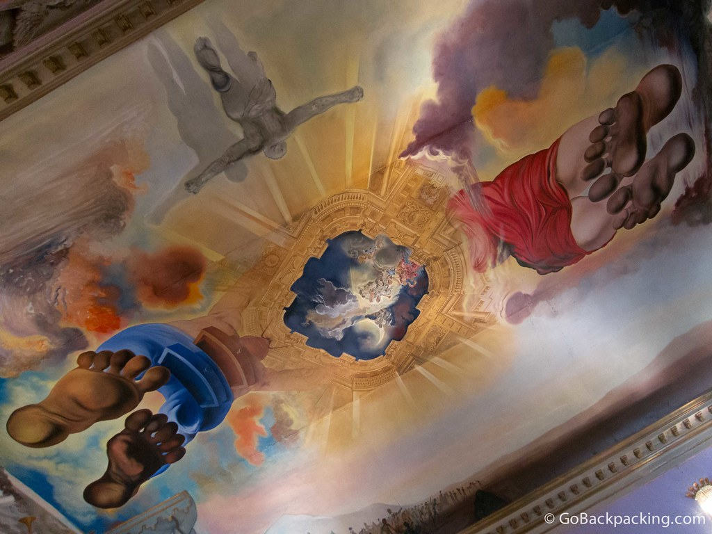 A massive ceiling fresco depicts Salvador Dalí (blue) and his wife, Gala Dalí, ascending toward heaven.