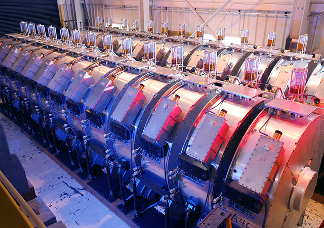 "DARHT's electron accelerators use large, circular aluminum structures to create magnetic fields that  focus and steer a stream of electrons down the length of the accelerator.  Tremendous electrical energy is added along the way.  When the stream of high-speed electrons exits the accelerator it is ""stopped"" by a tungsten target resulting in an intense burst of x-rays that are used to create digital images of mock nuclear devices as they implode."