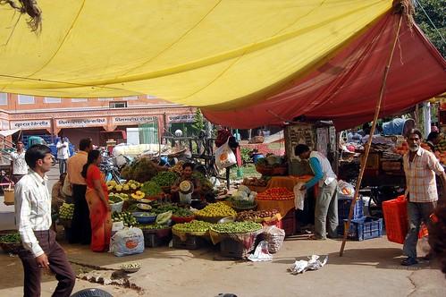 Unter einem Sonnensegel bietet eine Marktfrau ihre Waren an.