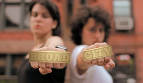 the two women who created Broad City punching the camera wearing jewelry that reads Broad City