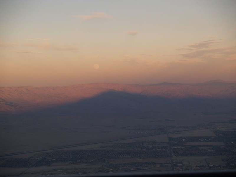The full moon rises as we view the sunset shadow of San Jacinto Peak from the Palm Springs Tram