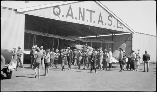 Les Holden's de Havilland DH61 Giant Moth biplane airliner G-AUHW 'Canberra' in a Qantas hangar is examined by crowd, Longreach, Queensland, 25 April 1929.