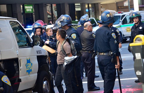 Cop with paint on riot helmet as #fuckcolumbus loaded into paddy wagon
