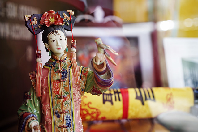 Chinese doll behind glass