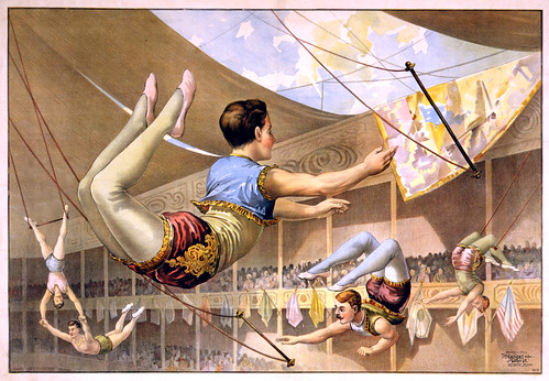 Five male trapeze artists performing at a circus, 1890