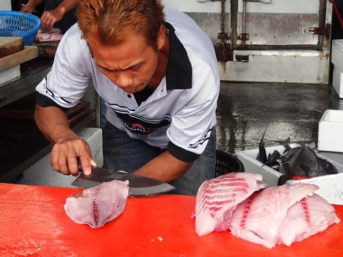 魚市裡,攤販孰練地替「琵琶魚」剝皮取肉