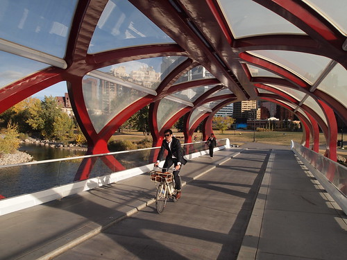 Classy suit on a classy bike on a classy bridge