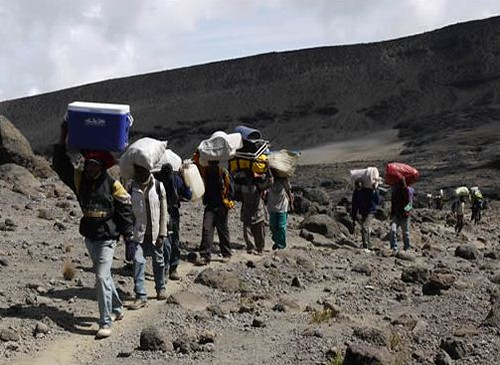 Porters carry equipment to the Lava Tower on Day Five of The Xpedition