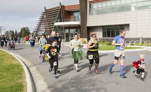 Racers run past the Kenaitze Indian Tribe's Dena'ina Wellness Center at the start of the CASA Superhero 5-kilometer run/walk on Saturday morning. The event raised funds for the tribe's Court Appointed Special Advocates program.